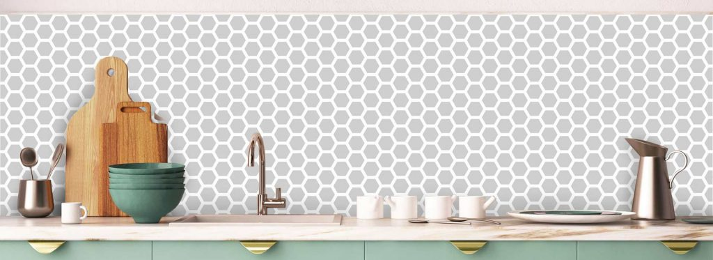 geometric style printed patterned splashback or backsplash in a light green kitchen with gold accents