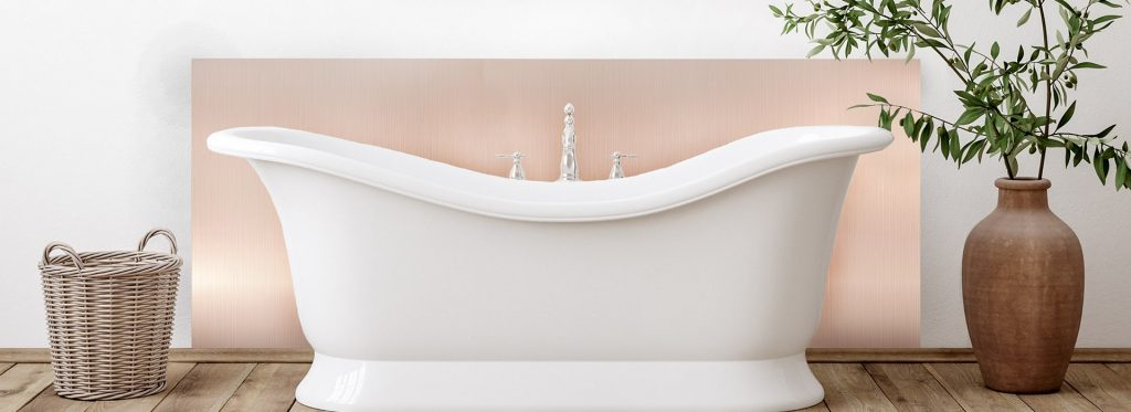 Rose gold splashback in traditional bathroom with white roll top bath and greenery.